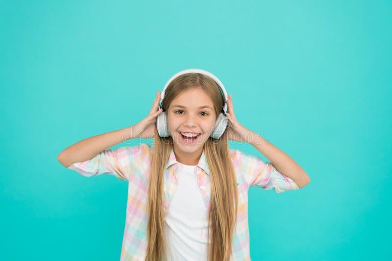É realmente um fan de música grande A criança pequena feliz aprecia a música que joga nos fones de ouvido Criança da menina que e foto de stock royalty free