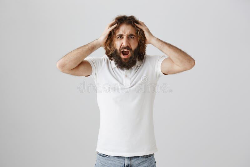 É você em sua mente, como poderia você a faz Retrato do homem adulto louco e irritado com terra arrendada longa do cabelo encarac imagens de stock