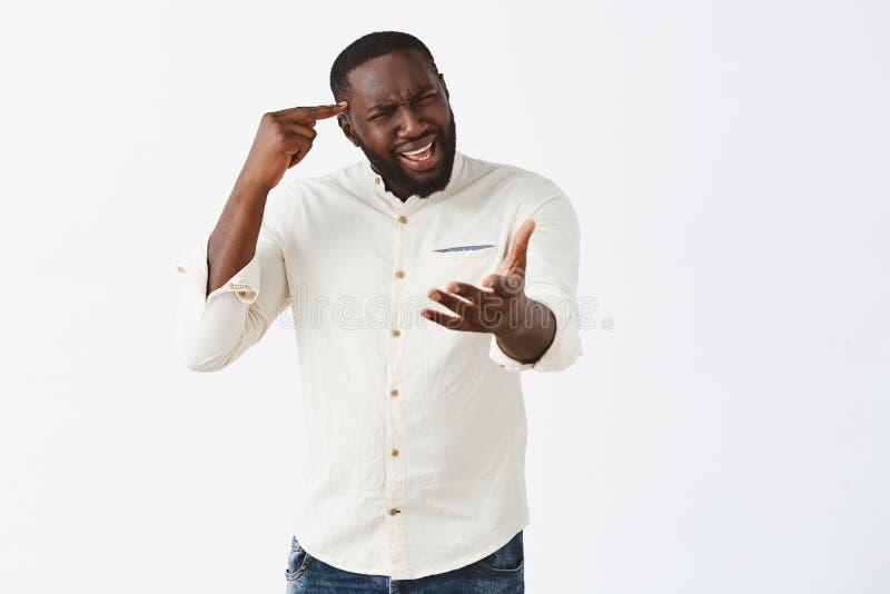 É você estúpido ou insano Annoyed confundiu e desagradou o afro-americano bonito no equipamento ocasional, gesticulando com foto de stock