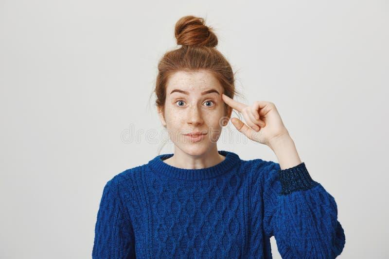 É você fora de sua mente Mulher europeia nova atrativa com cabelo e as sardas vermelhos com índice do rolamento do penteado do bo fotos de stock royalty free