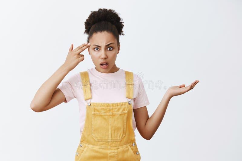 É você insano ou mudo O retrato do desagradado mijado e irritado questionou fêmea com a pele escura, shrugging com fotografia de stock