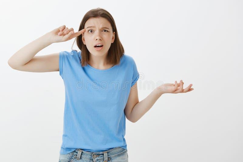 É você perdeu sua mente Pissed confundiu a mulher europeia engraçada no equipamento ocasional, aumentando a palma no gesto à nora fotos de stock