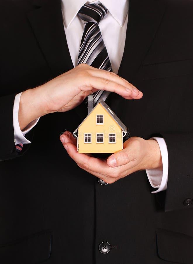 É você segurou o conceito isolado sobre o backg branco Modelo da casa nas mãos do homem de negócios foto de stock