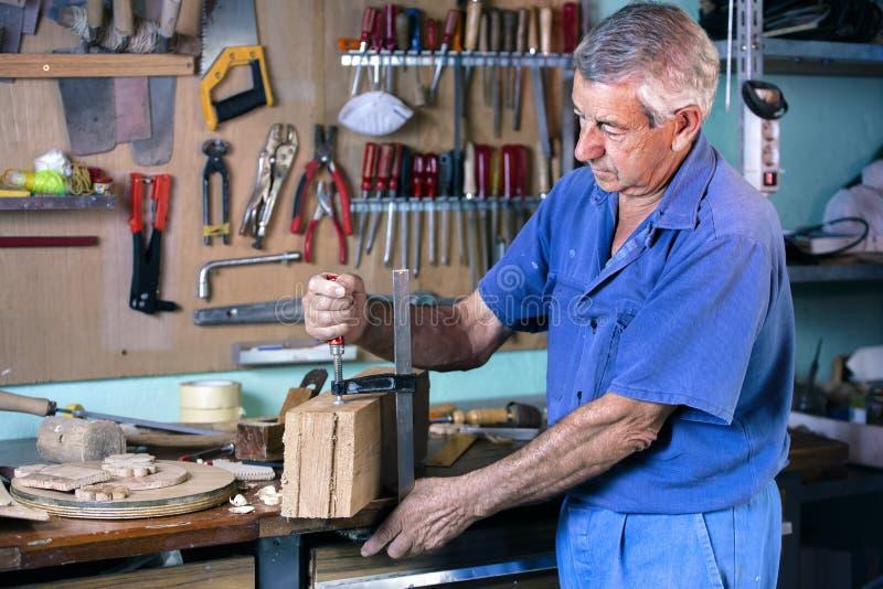 Ébéniste découpant le bois avec la bride de vis dans l'établi images stock