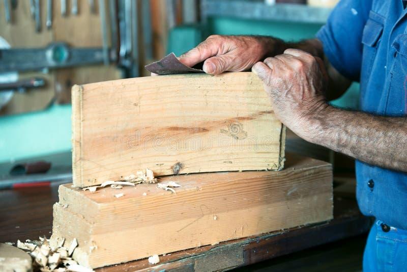 Ébéniste travaillant avec le papier sablé dans le banc dans le garage à ho photos stock
