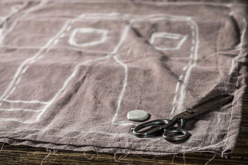 Ébauche de ciseaux, de tissu et de tailleur des pantalons en travaillant l'atelier photo libre de droits