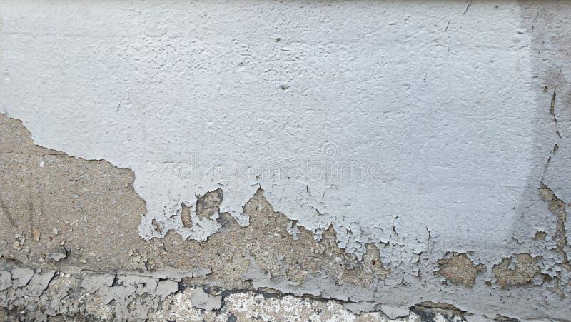 Ébrèchement du mur affligé de ciment peint par blanc image libre de droits