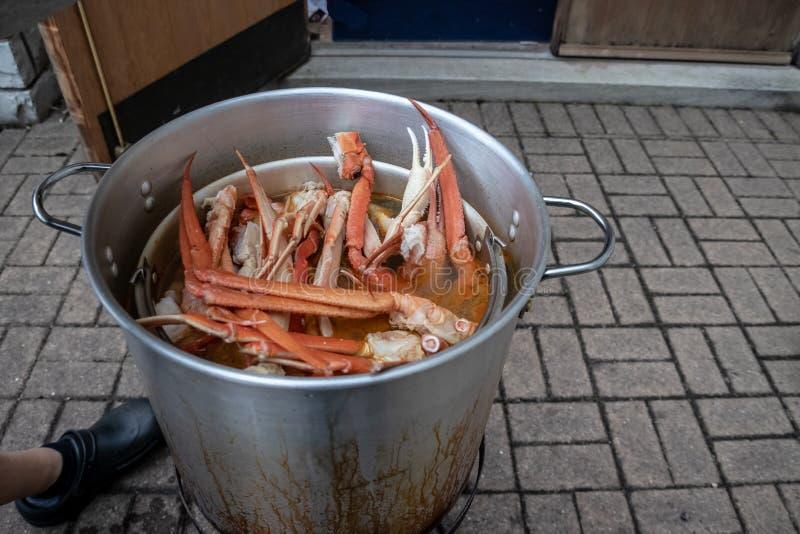 Ébullition de fruits de mer dans le grand pot avec le pied du ` s de chef à côté de faire cuire le foo photo libre de droits