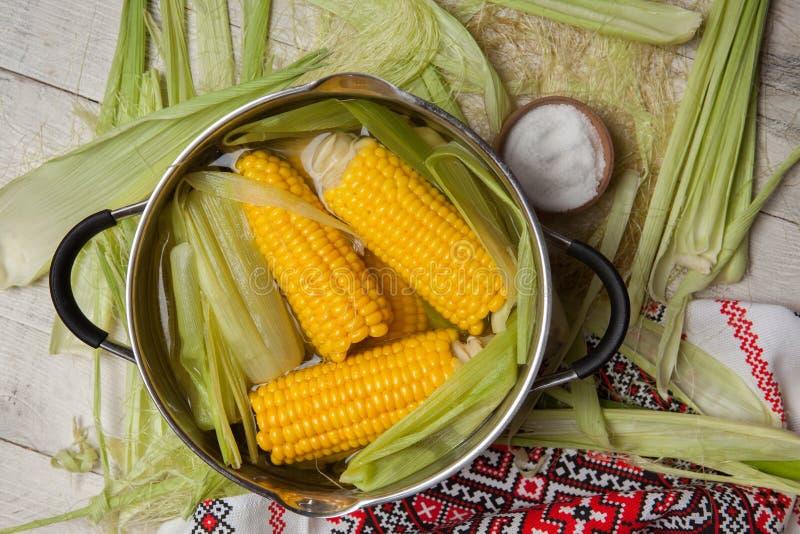 Ébullition de maïs avec du sel maïs cuit dans le pot sur la table en bois photo libre de droits