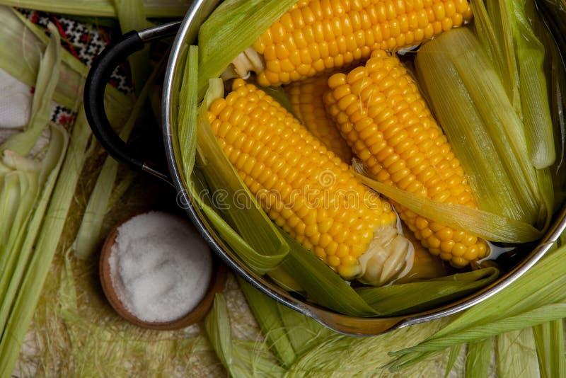 Ébullition de maïs avec du sel maïs cuit dans le pot sur la table en bois image libre de droits