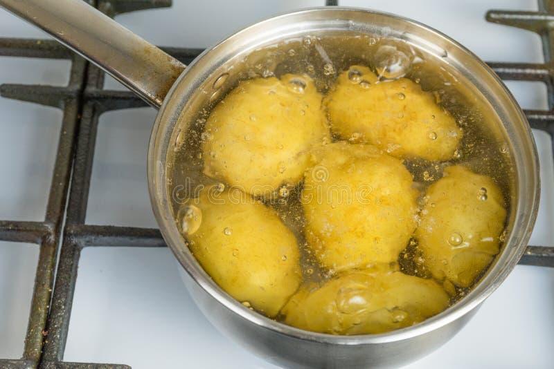 Ébullition non traitée de pommes de terre dans un pot sur une cuisinière à gaz photos stock