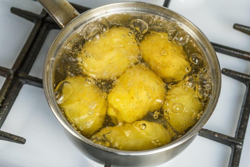 Ébullition non traitée de pommes de terre dans un pot sur une cuisinière à gaz photos libres de droits