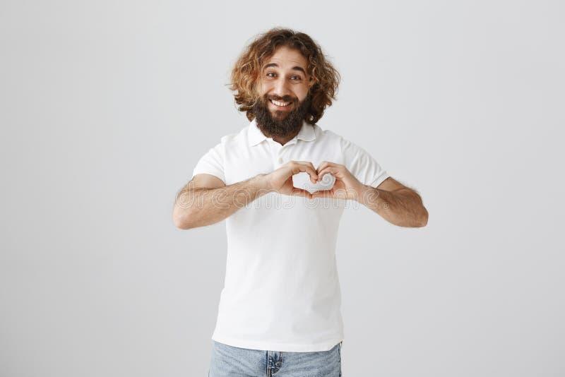 Écartez l'amour à travers le monde Portrait de type oriental amical et passionné avec la barbe faisant le geste entendu avec des  images libres de droits