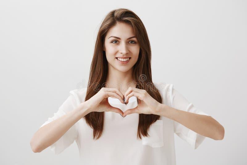 Écartez l'amour en monde Portrait de l'amie romantique belle se tenant sur le fond gris avec le sourire mignon image stock