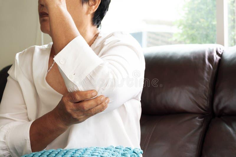 Écartez la douleur/blessure d'un coup de coude, dame âgée souffrant de la douleur de coude, concept de problème de santé photos stock