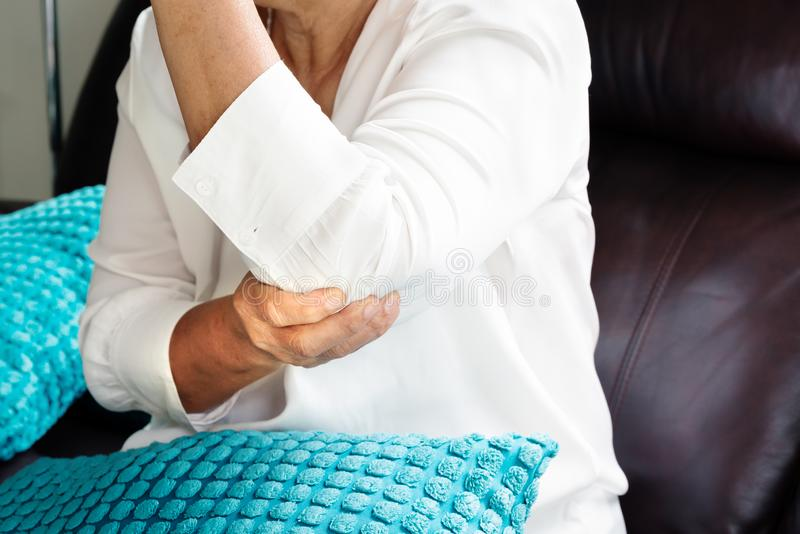 Écartez la douleur/blessure d'un coup de coude, dame âgée souffrant de la douleur de coude, concept de problème de santé image libre de droits