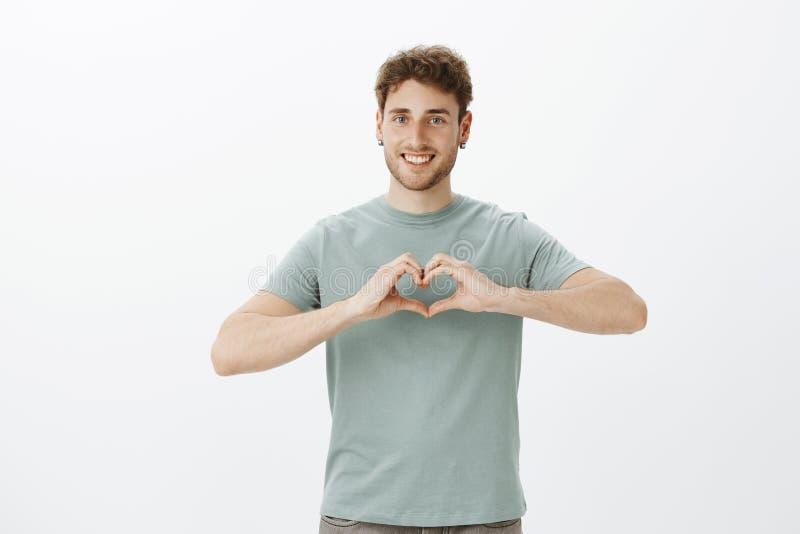 Écartez la guerre d'amour pas Portrait de type positif à l'air amical heureux dans des boucles d'oreille montrant le geste de coe image stock