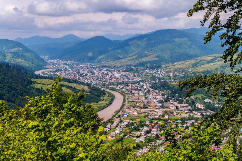 Écartez la ville sur les zigzags du littoral de la rivière parmi les hautes montagnes dans la perspective d'éloigné photo stock