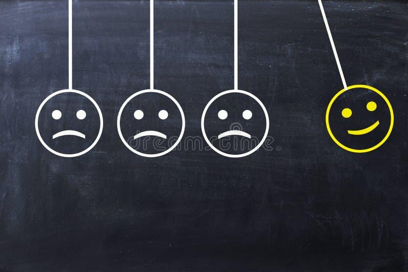 Écartez le concept de bonheur avec les visages heureux et tristes sur le berceau de newton's sur le tableau noir photographie stock libre de droits
