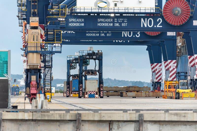 Écartez les jambes le transporteur prenant des conteneurs d'un bateau à la botanique gauche photographie stock