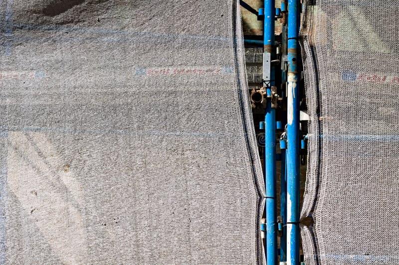Échafaudage en acier bleu sur un chantier de construction avec une tôle blanche de protection Italie, Europe images libres de droits