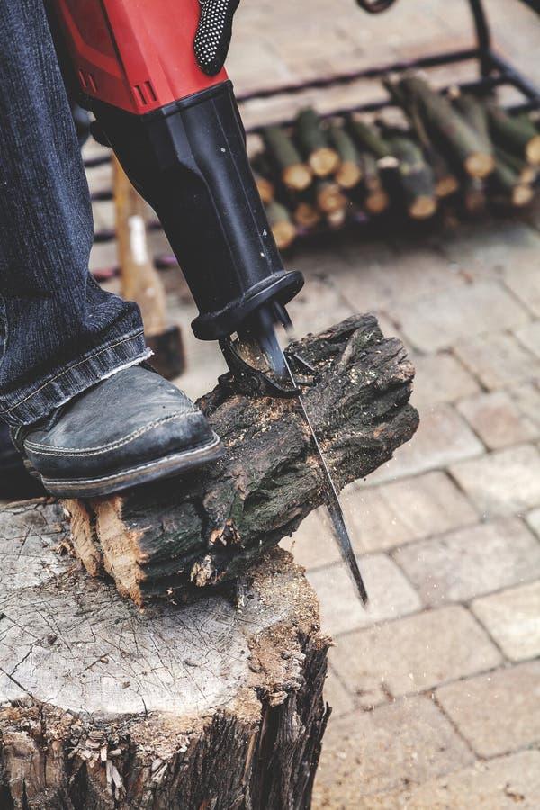 Échange de la scie de puissance sciant autour du plan rapproché de bois de construction photo stock