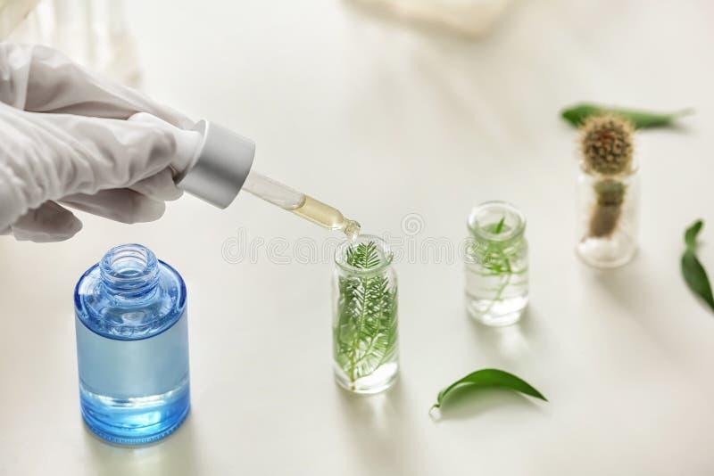 Échantillon d'égoutture de femme dans la bouteille avec l'usine sur la table dans le laboratoire photos stock