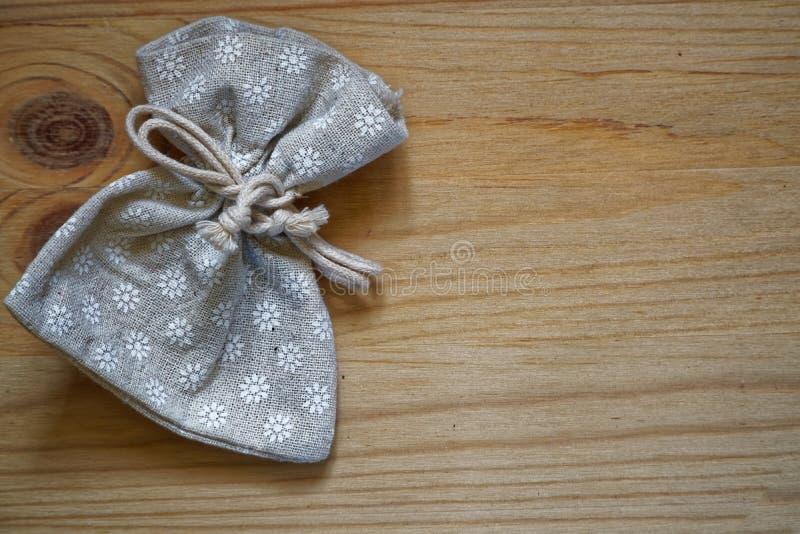Échantillon de carte postale, poche grise neutre de cadeau sur le fond en bois avec le copyspace gratuit pour le texte de salutat photos stock