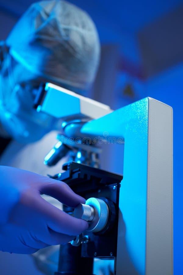 Échantillon de examen de scientifique avec le microscope photographie stock