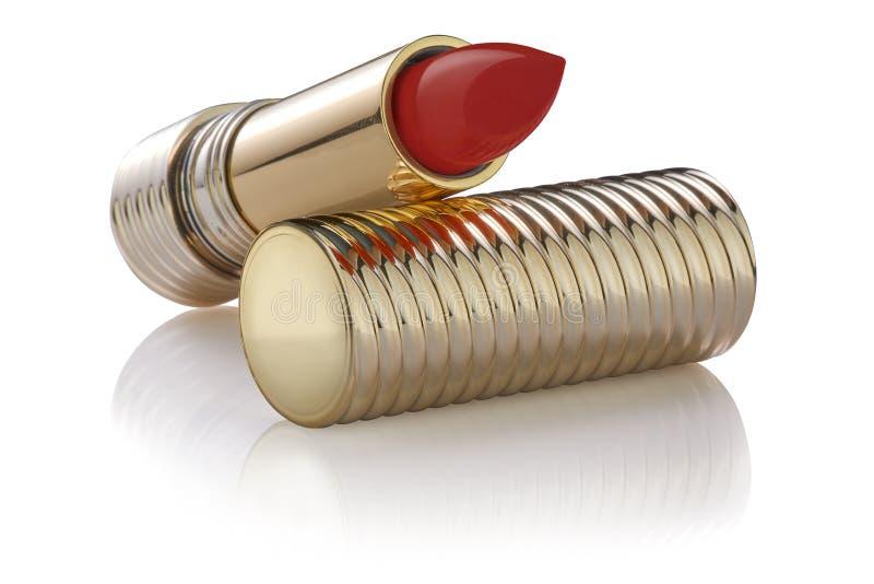 Échantillon de rouge à lèvres de couleur rouge dans le tube d'or ouvert de luxe sur un couvercle d'or, réfléchi sur la surface, d photo libre de droits