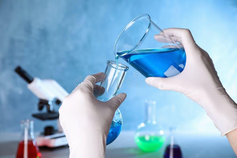 Échantillon de versement auxiliaire dans le flacon en verre dans le laboratoire de chimie images stock