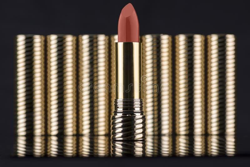 Échantillon pâle de rouge à lèvres de couleur rouge dans un tube d'or pointu, avec d'autres tubes d'or brouillés sur un fond noir images stock