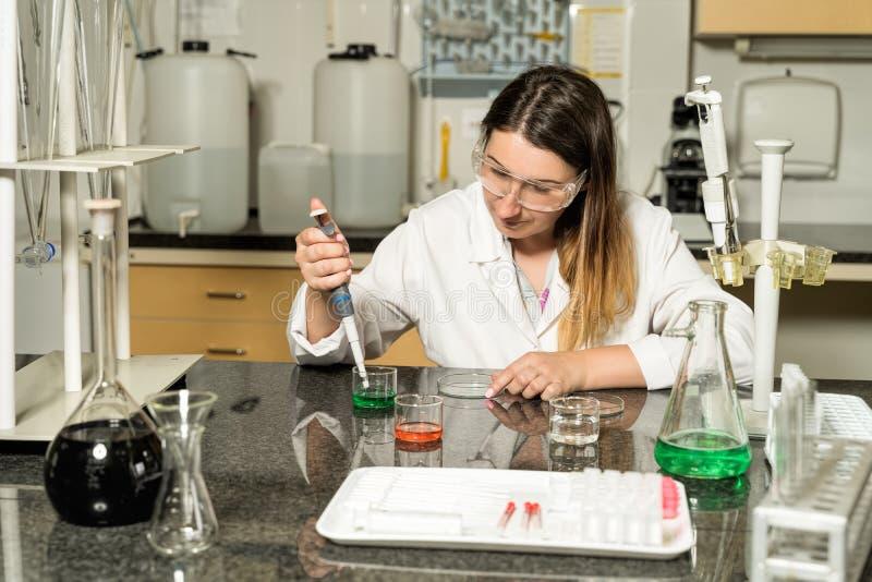 Échantillonnage femelle de technicien de laboratoire de Moyen Âge avec la solution liquide chimique de pipette dans le laboratoir image stock