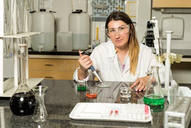 Échantillonnage femelle de technicien de laboratoire de Moyen Âge avec la solution liquide chimique de pipette dans le laboratoir photographie stock