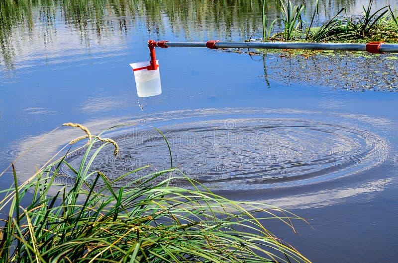 Échantillons de prise de l'eau pour l'essai en laboratoire Le concept - analyse de la pureté de l'eau, environnement, écologie image stock