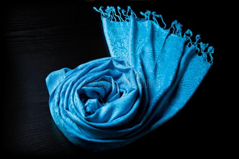 Écharpe bleue de cachemire sur un fond noir photographie stock