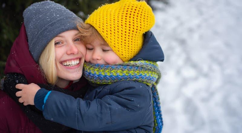 Écharpe chaude de chapeau de maman et de bébé Femme avec le fond neigeux de sourire de nature d'hiver de fils No?l et an neuf L'h images stock