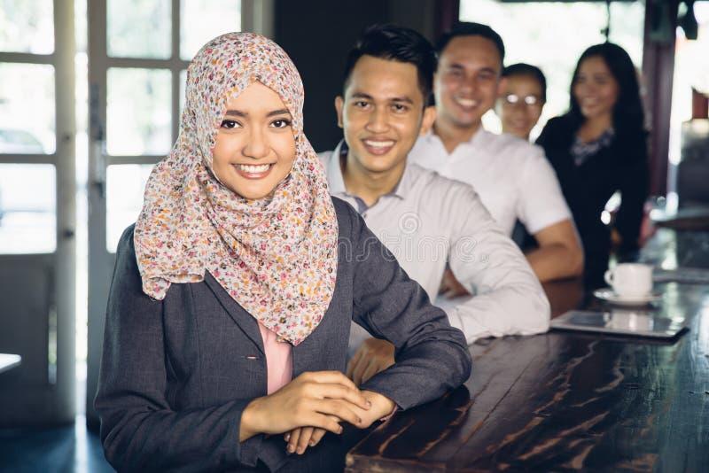 Écharpe de port de femme d'affaires musulmane occasionnelle se tenant devant h photos libres de droits