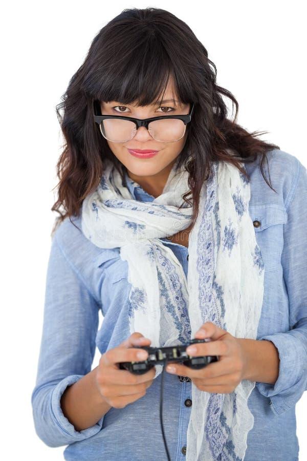 Écharpe de port et verres de belle femme jouant des jeux vidéo photos stock