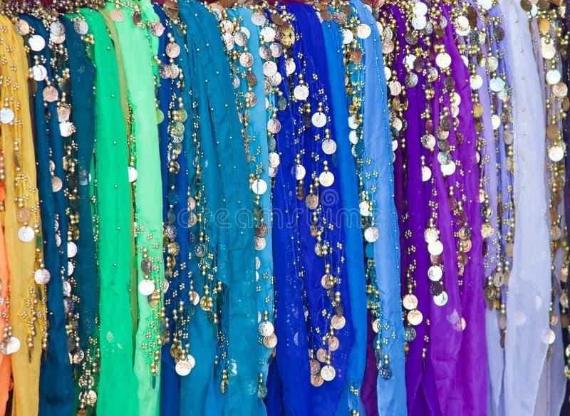 Écharpes multicolores accrochant avec les pièces d'or et en argent images stock