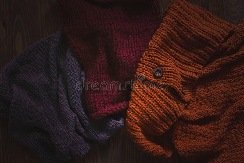 Écharpes tricotées sur le fond en bois, automne photographie stock