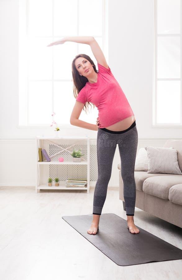 Échauffement de femme enceinte étirant la formation à l'intérieur photo stock