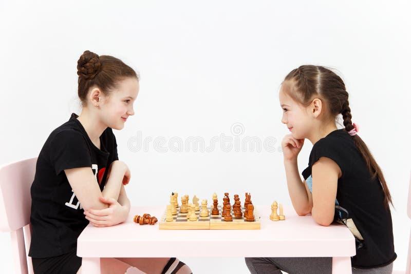 Échecs de jeu de deux filles sur le fond blanc image libre de droits