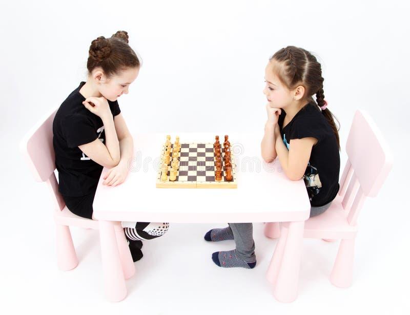 Échecs de jeu de deux filles sur le fond blanc photos stock