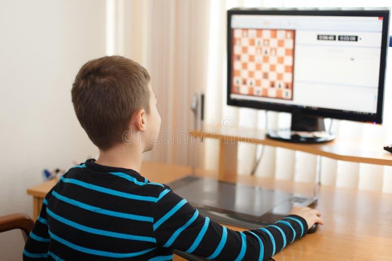 Échecs en ligne de jeu de petit garçon à la maison photos libres de droits