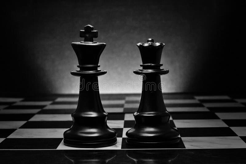 Échecs Roi et reine noirs sur le conseil Les chiffres les plus puissants photographie stock