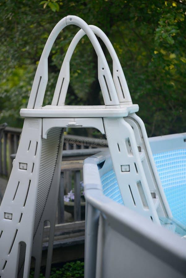 Échelle blanche de piscine se reposant dans la piscine dans le jour d'été chaud image libre de droits