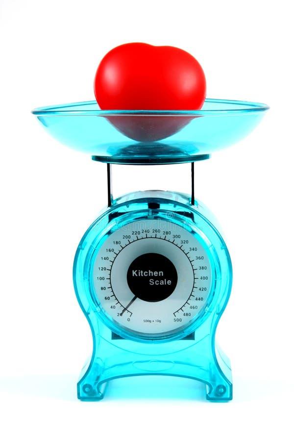 Échelle bleue de cuisine mesurant le poids d'un coeur images libres de droits