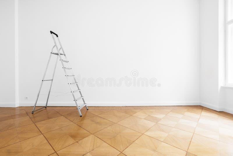 Échelle dans la chambre vide avec le mur blanc et le plancher en bois images libres de droits