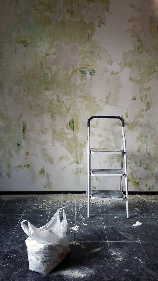 Échelle dans la chambre vide, mur gris de grounge, réparation photos libres de droits